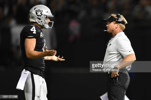 Derek Carr of the Oakland Raiders speaks with head coach Jon Gruden during their NFL game against the Los Angeles Rams at Oakland-Alameda County...