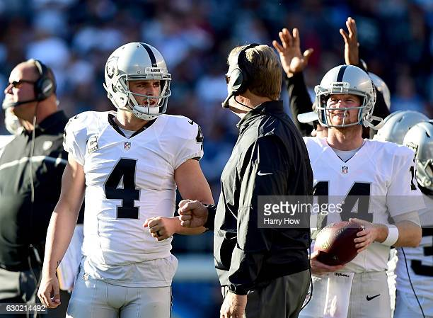 Derek Carr of the Oakland Raiders talks with head coach Jack Del Rio during a video replay challenge resulting in a touchdown to Michael Crabtree...