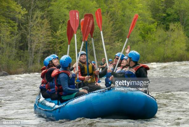 A group of rafters celebrate a successful run of the challenging Popular Falls rapids on the Dead River during a trip with Magic Falls Rafting...