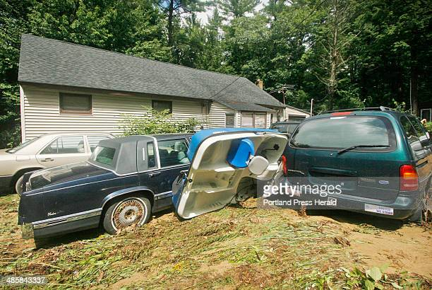 A paddle boat rests against cars parked in front of James Cavallaro's house on Comanche Lane in West Lebanon Friday Aug 8 2008 The stream that runs...