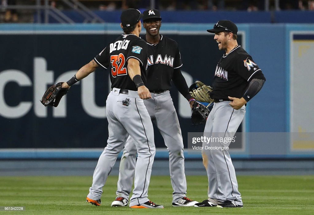 Derek Dietrich #32, Cameron Maybin #1 and J.B. Shuck #3 of the Miami Marlins celebrate after their 8-6 win in the outfield against the Los Angeles Dodgers in the MLB game at Dodger Stadium on April 25, 2018 in Los Angeles, California.