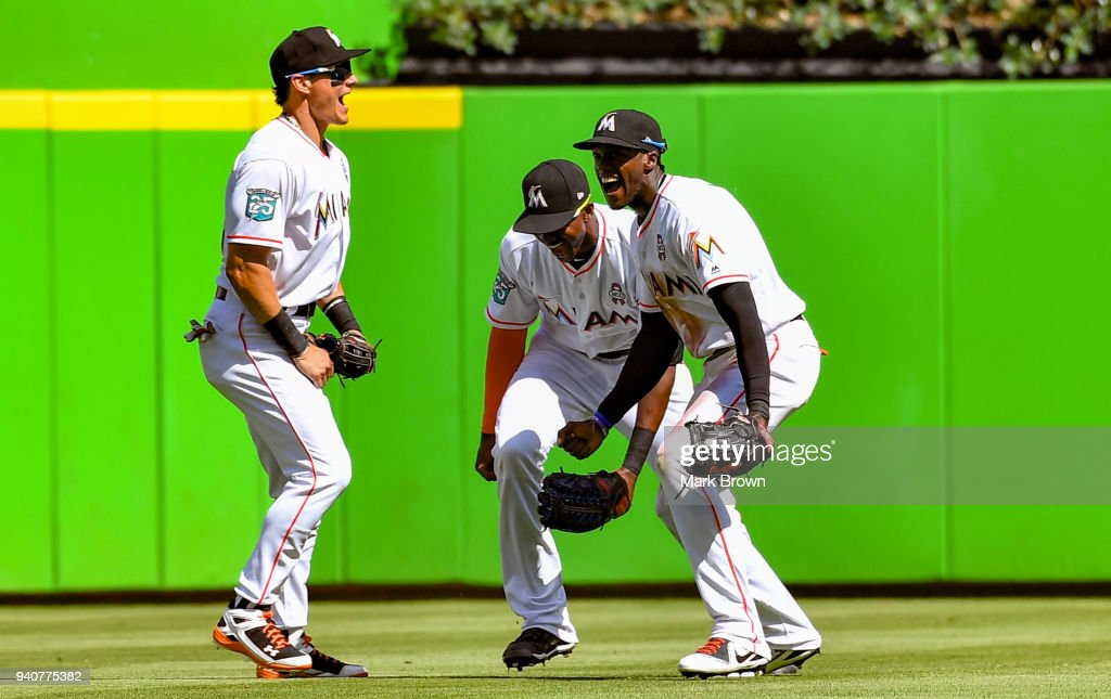 Derek Dietrich #32, Lewis Brinson #9 and Cameron Maybin #1 of the Miami Marlins celebrate after the game against the Chicago Cubs at Marlins Park on April 1, 2018 in Miami, Florida.