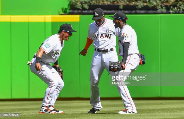 Derek Dietrich Lewis Brinson and Cameron Maybin of the Miami Marlins celebrate after the game against the Chicago Cubs at Marlins Park on April 1...