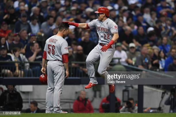 Derek Dietrich of the Cincinnati Reds celebrates a home run with third base coach JR House during the third inning of a game against the Milwaukee...