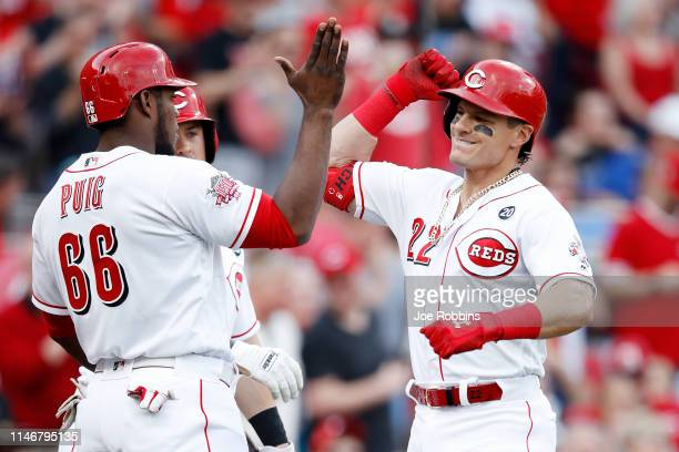 Derek Dietrich of the Cincinnati Reds celebrates with teammate Yasiel Puig after hitting a three-run home run in the first inning against the San...