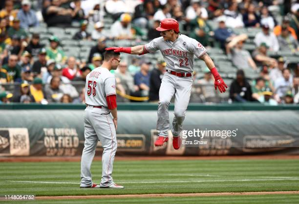 Derek Dietrich of the Cincinnati Reds taps the head of third base coach JR House as he rounds the bases after he hit a tworun home run in the first...