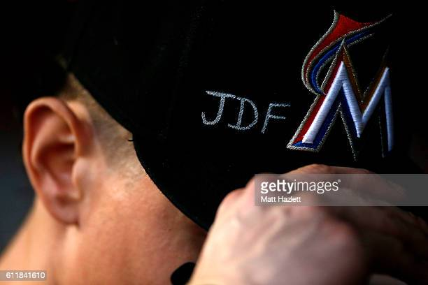 Derek Dietrich of the Miami Marlins adjusts his hat which displays support for Miami Marlins pitcher Jose Fernandez who died in a boating accident in...
