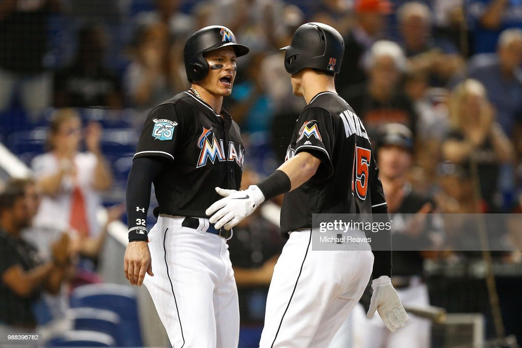 Derek Dietrich #32 of the Miami Marlins celebrates with Brian Anderson #15 after he hit a two-run home run in the sixth inning against the New York Mets at Marlins Park on June 30, 2018 in Miami, Florida.