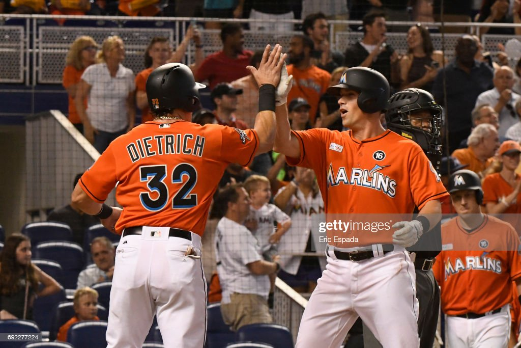 Derek Dietrich #32 of the Miami Marlins high fives Tyler Moore #28 after he hit a three-run home run in the second inning against the Arizona Diamondbacks at Marlins Park on June 4, 2017 in Miami, Florida.