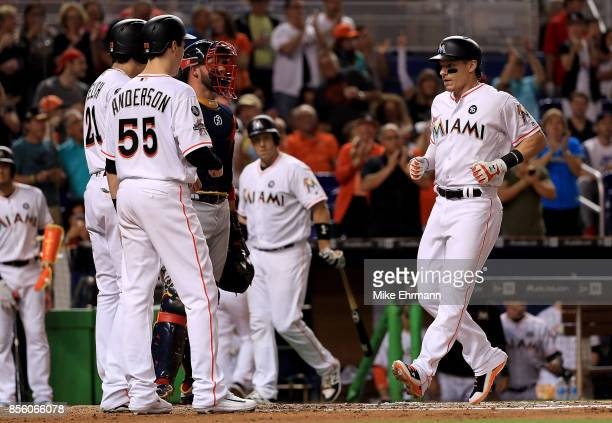 Derek Dietrich of the Miami Marlins is congratulated by Christian Yelich and Brian Anderson after a three run home run in the first inning during a...