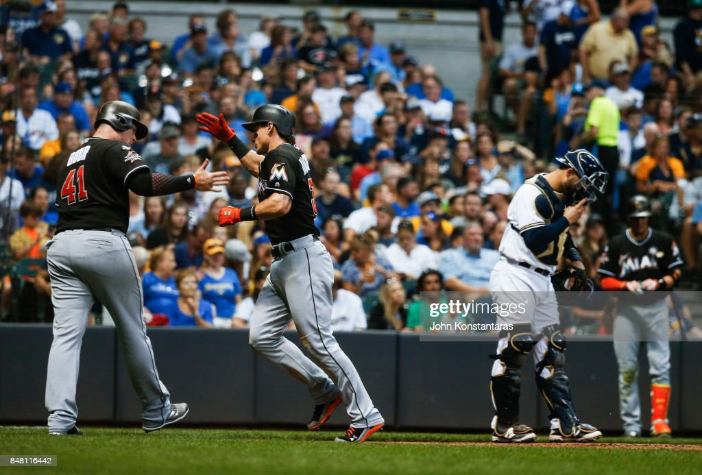 Derek Dietrich #32 of the Miami Marlins is greeted by Justin Bour #41 after his 2-run home run during the third inning against the Milwaukee Brewers at Miller Park on September 16, 2017 in Milwaukee, Wisconsin.