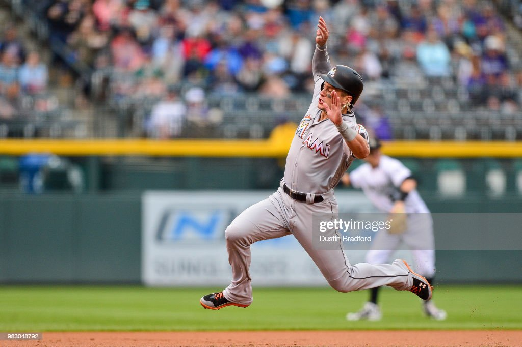 Derek Dietrich #32 of the Miami Marlins jumps before sliding safely into third base after advancing from second base in the first inning of a game against the Colorado Rockies at Coors Field on June 24, 2018 in Denver, Colorado.