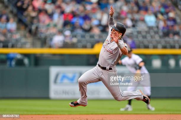 Derek Dietrich of the Miami Marlins jumps before sliding safely into third base after advancing from second base in the first inning of a game...