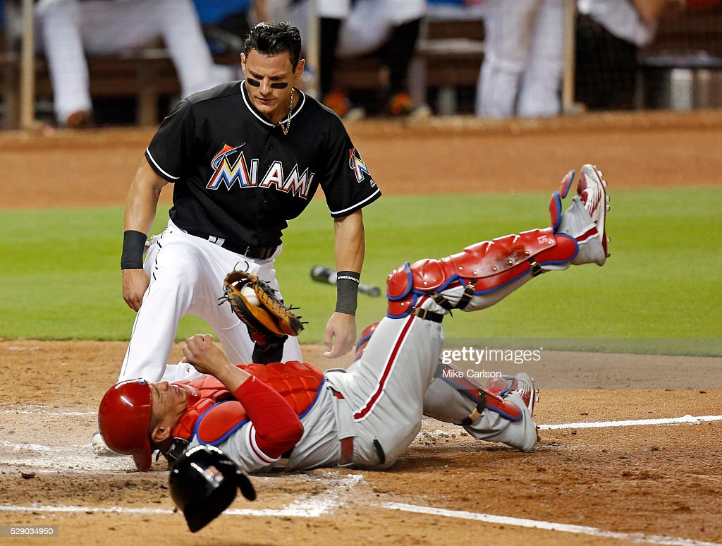 Derek Dietrich #32 of the Miami Marlins looks to see if Carlos Ruiz #51 of the Philadelphia Phillies holds on to the ball after a collision during the fifth inning of a game at Marlins Park on May 7, 2016 in Miami, Florida.