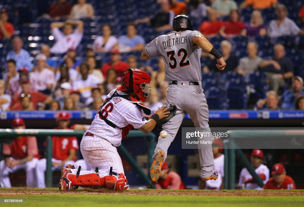 Derek Dietrich #32 of the Miami Marlins scores a run as Jorge Alfaro #38 of the Philadelphia Phillies can't hang onto the ball in the seventh inning during game two of a doubleheader at Citizens Bank Park on August 22, 2017 in Philadelphia, Pennsylvania. The Marlins won 7-4.