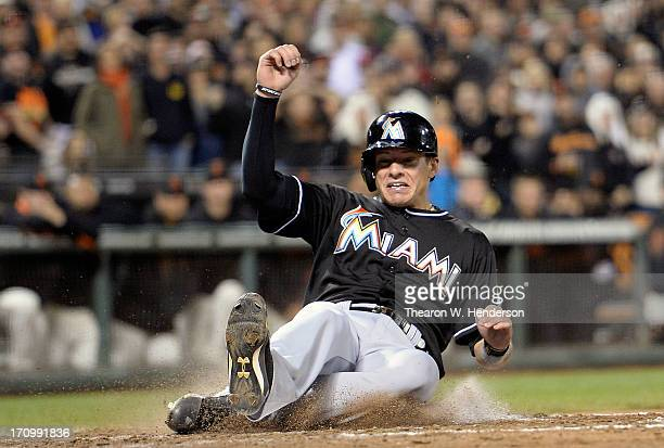 Derek Dietrich of the Miami Marlins slides in safe at home scoring on a pitchhit RBI single from Marcell Ozuna in the eighth inning against the San...