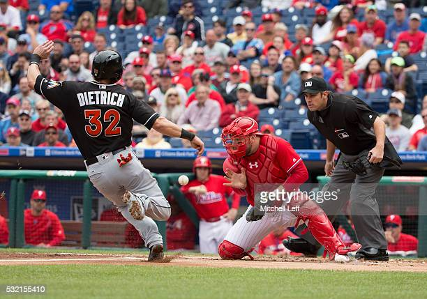 Derek Dietrich of the Miami Marlins slides past Cameron Rupp of the Philadelphia Phillies to score a run in the top of the first inning at Citizens...