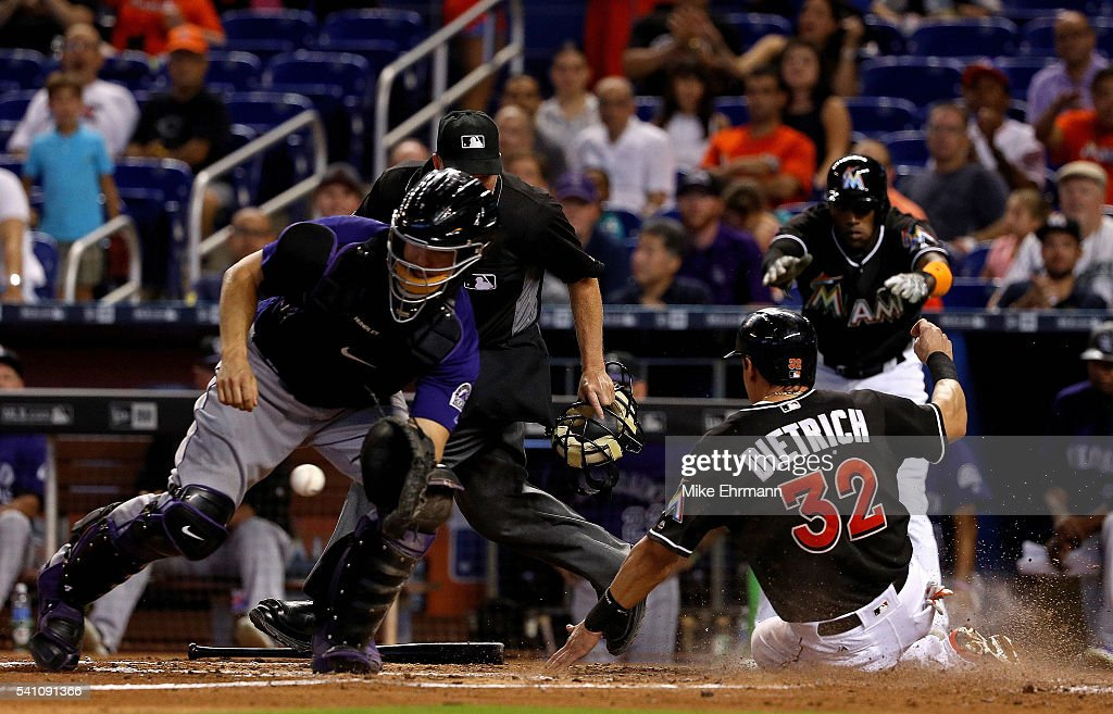 Derek Dietrich #32 of the Miami Marlins slides past the tag of Nick Hundley #4 of the Colorado Rockies during a game at Marlins Park on June 18, 2016 in Miami, Florida.