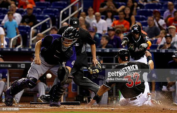 Derek Dietrich of the Miami Marlins slides past the tag of Nick Hundley of the Colorado Rockies during a game at Marlins Park on June 18, 2016 in...