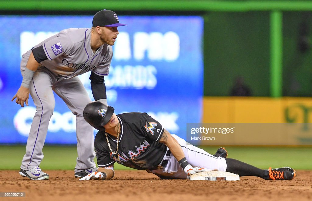 Derek Dietrich #32 of the Miami Marlins with a pinch hit double slides into second in the ninth inning against the Colorado Rockies at Marlins Park on April 27, 2018 in Miami, Florida.