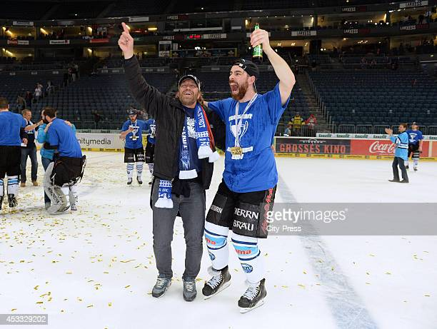 Derek Dinger celebrates the championship with a fan after game seven of the DEL playoff final on April 29, 2014 in Cologne, Germany.