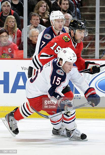 Derek Dorsett and Jeff Carter of the Columbus Blue Jackets and Andrew Brunette of the Chicago Blackhawks skate up the ice during the NHL game on...