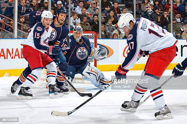 Derek Dorsett fights for position with Jason Strudwick and Dwayne Roloson of the Edmonton Oilers while Andrew Murray of the Columbus Blue Jackets...