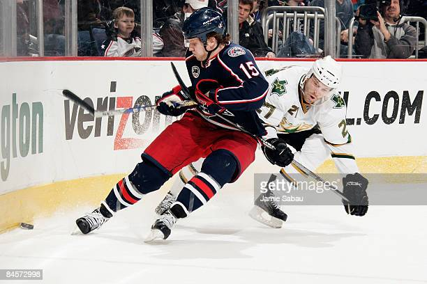 Derek Dorsett of the Columbus Blue Jackets and Andrew Hutchinson of the Dallas Stars chase down a loose puck into the corner during the first period...