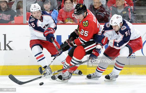 Derek Dorsett of the Columbus Blue Jackets reaches across Viktor Stalberg of the Chicago Blackhawks as they chase after the puck while Fedor Tyutin...