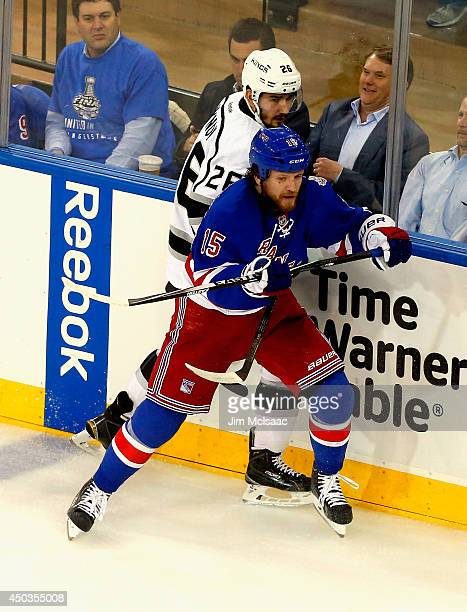Derek Dorsett of the New York Rangers checks Slava Voynov of the Los Angeles Kings during the first period of Game Three of the 2014 NHL Stanley Cup...