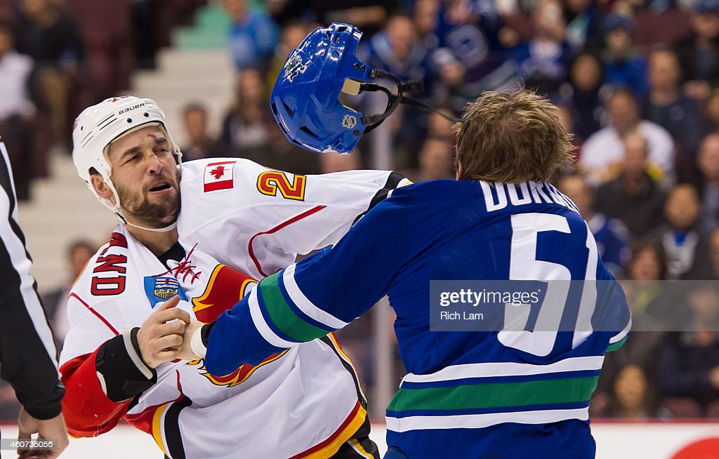 Derek Dorsett #51 of the Vancouver Canucks and Deryk Engelland #29 of the Calgary Flames fight during the first period in NHL action on December 20, 2014 at Rogers Arena in Vancouver, British Columbia, Canada.