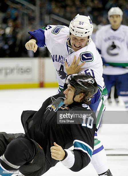 Derek Dorsett of the Vancouver Canucks fights with Andrew Desjardins of the San Jose Sharks at SAP Center on November 6 2014 in San Jose California