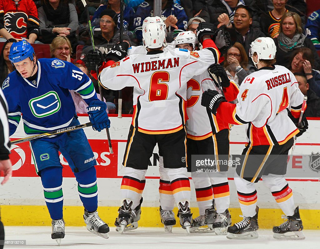 Derek Dorsett #51 of the Vancouver Canucks skates away as Dennis Wideman #6 and Kris Russell #4 of the Calgary Flames join the goal celebration during their NHL game at Rogers Arena January 10, 2015 in Vancouver, British Columbia, Canada. Calgary won 1-0.