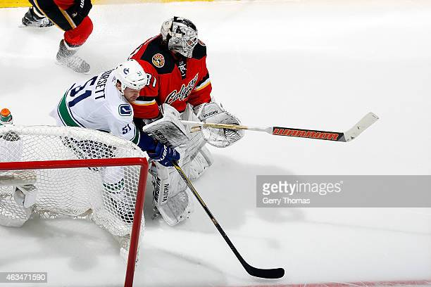Derek Dorsett of the Vancouver Canucks tries to steal the puck from Karri Ramo of the Calgary Flames at Scotiabank Saddledome on February 14 2015 in...