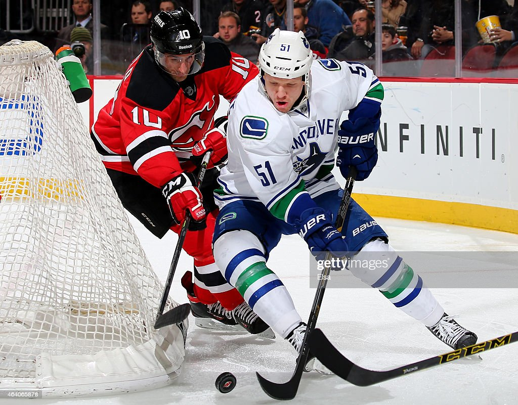 Derek Dorsett #51 of the Vancouver Canucks wraps around the net as Peter Harrold #10 of the New Jersey Devils defends on February 20, 2015 at the Prudential Center in Newark, New Jersey.The New Jersey Devils defeated the Vancouver Canucks 4-2.
