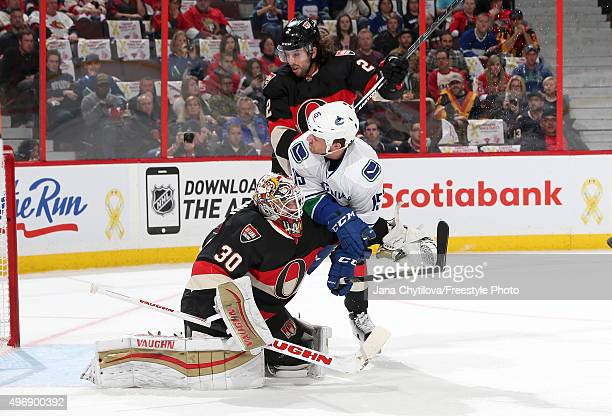 Derek Dorsett the Vancouver Canucks crashes into Andrew Hammond and Jared Cowen of the Ottawa Senators during an NHL game at Canadian Tire Centre on...