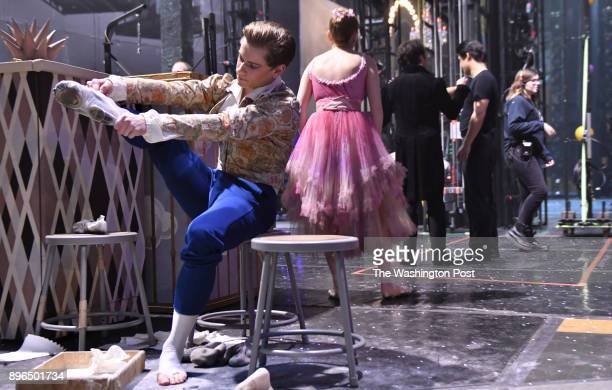 Derek Dunn left a dancer with the Boston Ballet applies rosin to his feet and ballet slippers during intermission backstage at The Nutcracker...