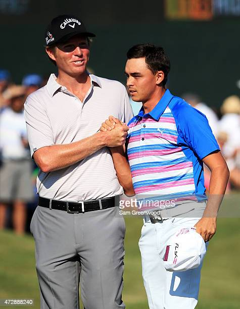 Derek Fathauer congratulates Rickie Fowler after Fowler finished at 12 under par during the final round of THE PLAYERS Championship at the TPC...