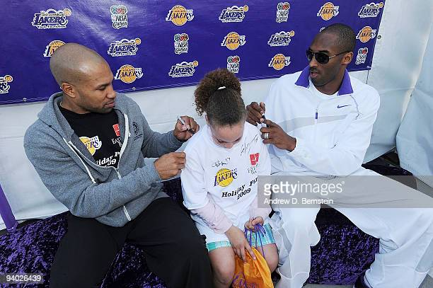 Derek Fisher and Kobe Bryant of the Los Angeles Lakers autographs a tshirt for a participant at the Los Angeles Lakers annual Holiday Party for kids...