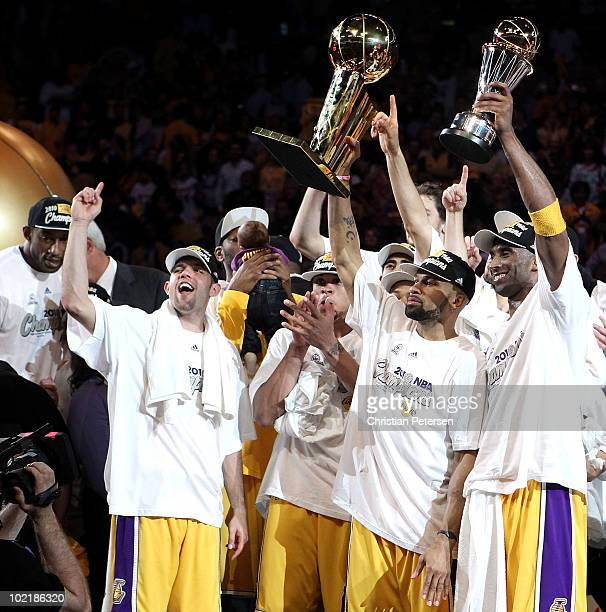 Derek Fisher and Kobe Bryant of the Los Angeles Lakers hold up the Larry O'Brien trophy and the Bill Russell Finals MVP trophy after the Lakers...