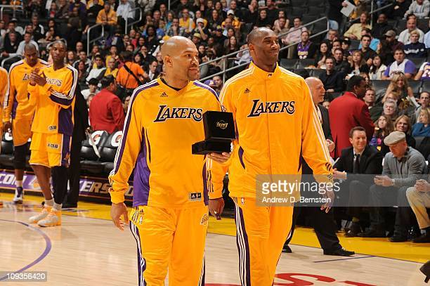 Derek Fisher and Kobe Bryant of the Los Angeles Lakers prepare to present Josh Powell of the Atlanta Hawks with a 200910 NBA Championship ring before...