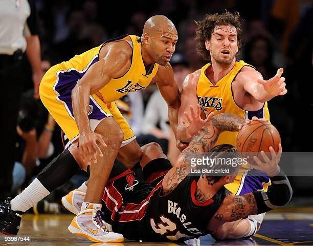 Derek Fisher and Pau Gasol of the Los Angeles Lakers try to get the ball from Michael Beasley of the Miami Heat at Staples Center on December 4 2009...