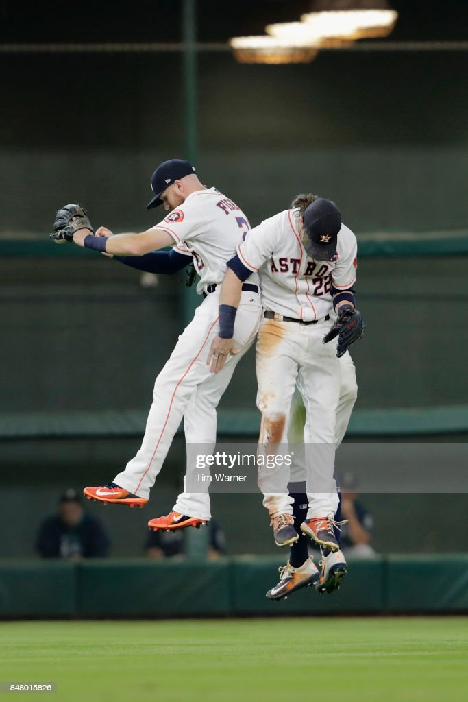 Derek Fisher #21, Josh Reddick #22, and George Springer #4 of the Houston Astros celebrate in the outfield after the game against the Seattle Mariners at Minute Maid Park on September 16, 2017 in Houston, Texas.