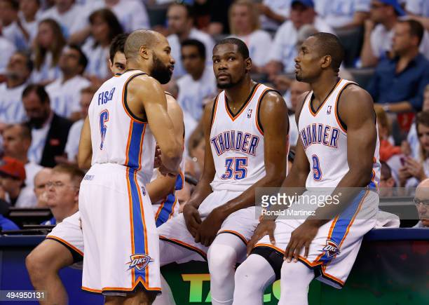 Derek Fisher Kevin Durant and Serge Ibaka of the Oklahoma City Thunder wait to enter the game against the San Antonio Spurs in the second half during...