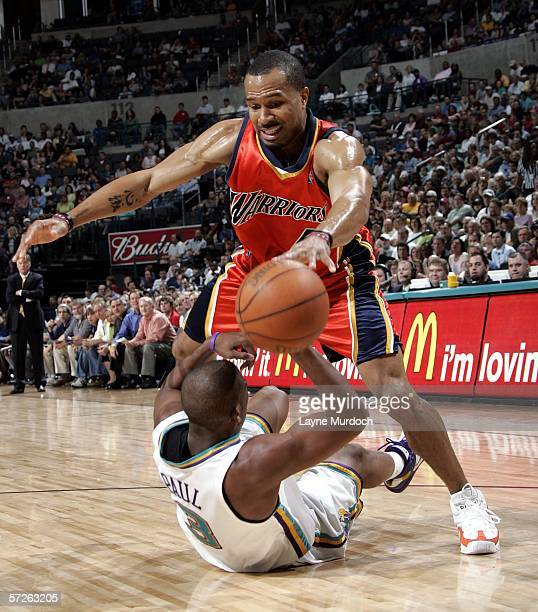 Derek Fisher of the Golden State Warriors dribbles over Chris Paul of the New Orleans/Oklahoma City Hornets during a game on April 5 2006 at the Ford...
