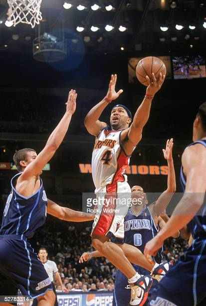 Derek Fisher of the Golden State Warriors drives to the basket for a layup against Kris Humphries of the Utah Jazz during the NBA game at The Arena...