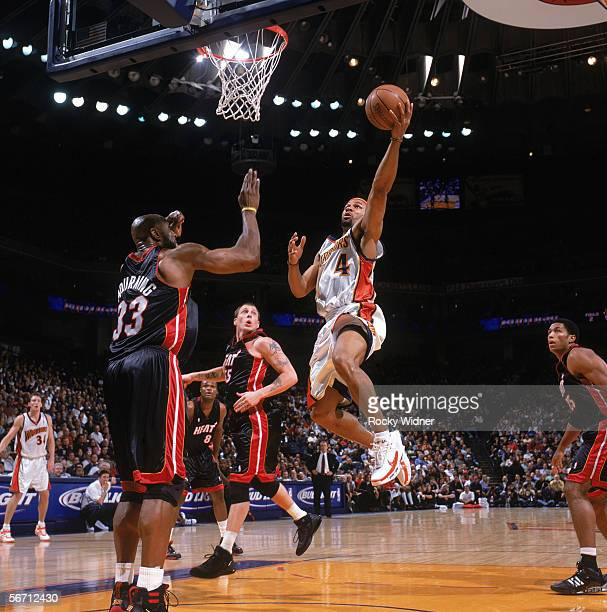Derek Fisher of the Golden State Warriors drives to the basket for a layup against Alonzo Mourning of the Miami Heat during a game at The Arena in...