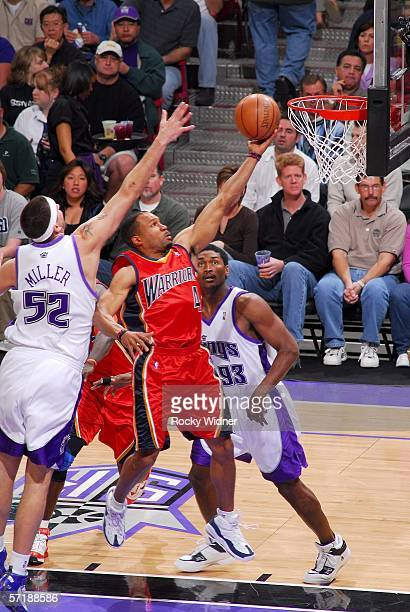 Derek Fisher of the Golden State Warriors takes the ball to the basket against Brad Miller and Ron Artest of the Sacramento Kings on March 26 2006 at...
