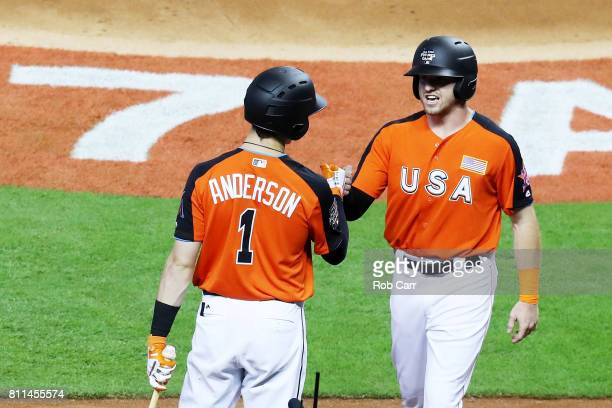 Derek Fisher of the Houston Astros and the US Team celebrates with Brian Anderson of the Miami Marlins and the US Team after scoring a run in the...