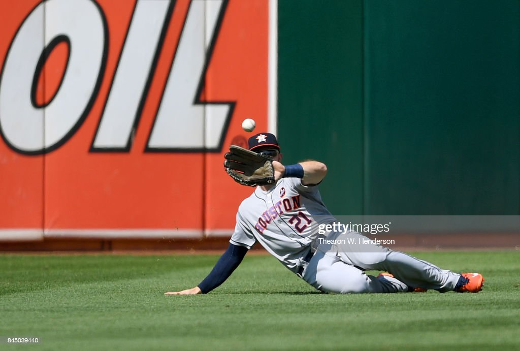 Derek Fisher #21 of the Houston Astros goes into a slide to catch a fly ball, taking a hit away from Boog Powell #3 of the Oakland Athletics in the bottom of the fourth inning during game one of a doubleheader at Oakland Alameda Coliseum on September 9, 2017 in Oakland, California.